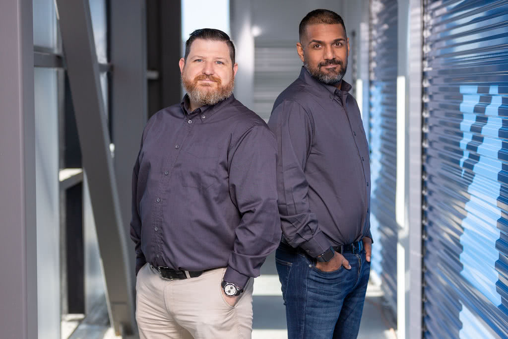 Storage Industry Experts, Chedwick Schultz and Ayaaz Jamal posing by storage units in the NationWide Pender facility