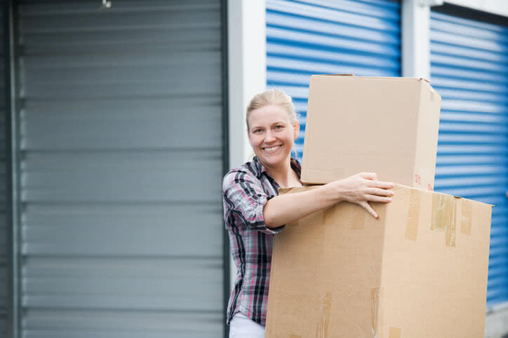 Satisfied and smiling customer holding boxes outside her rented NationWide Self Storage unit